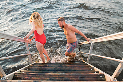 Couple walking into water - p312m2051793 by Viktor Holm