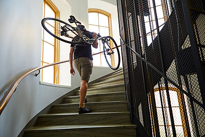 Sweden, Cyclist carrying bicycle on steps - p352m1350184 by Folio Images