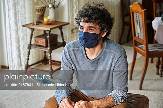 Man sitting on the floor with face mask, portrait - p1146m2187841 by Stephanie Uhlenbrock