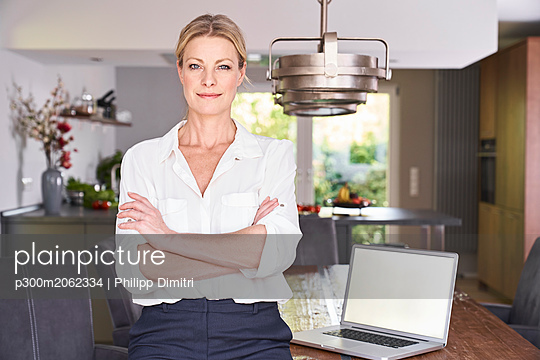 Portrait of confident businesswoman at home with laptop on table - p300m2062334 von Philipp Dimitri