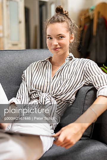 Young woman sitting ob couch, holding digital tabet, looking at camera - p300m2167446 by Peter Scholl