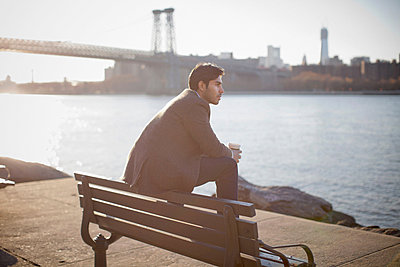 Man with cup of coffee on park bench - p924m757049f by Chad Springer