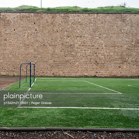 Deserted football field alongside old defensive wall, Akko, Israel - p1542m2173601 by Roger Grasas