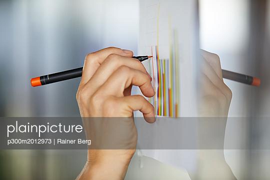 Hand drawing bar charts on paper at glass pane - p300m2012973 von Rainer Berg
