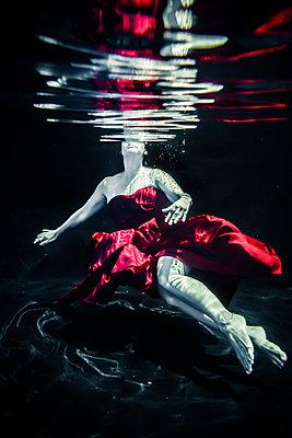 Frau im roten Kleid treibt Unterwasser - p1019m1461906 von Stephen Carroll