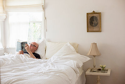Man lying in a bed with white linen, reading. - p1100m1080244 by Mint Images