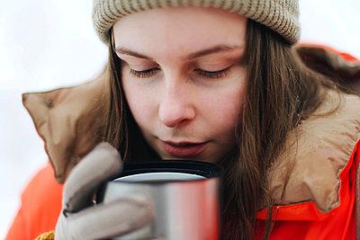 Woman  in orange jacket drinking hot tea outdoors in winter. - p1166m2255405 by Cavan Images
