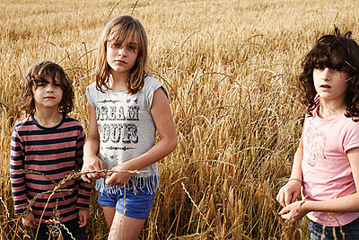 Three kids in a field - p1430m1503685 by Charlotte Bresson