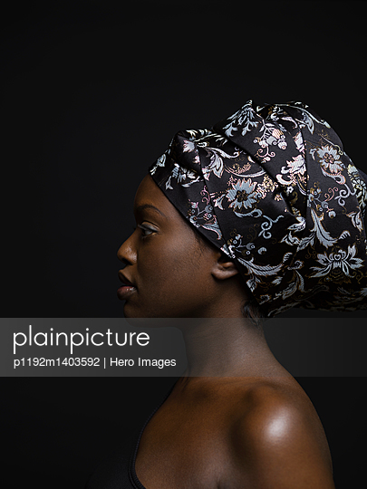 Profile portrait serious African American woman with bare shoulders and headscarf against black background - p1192m1403592 by Hero Images