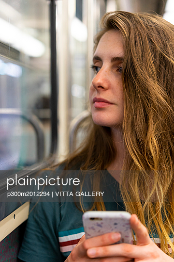 Portrait of young woman with smartphone in underground train - p300m2012294 von VITTA GALLERY