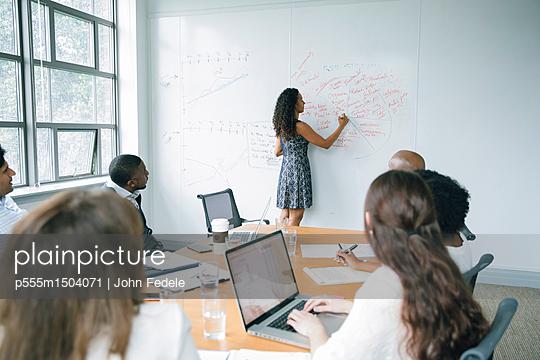 Businesswoman writing on whiteboard in meeting - p555m1504071 by John Fedele