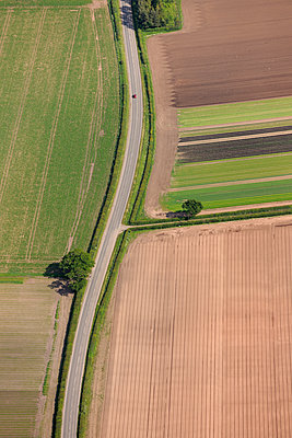 Aerial view of a country road with single car - p1048m2088097 by Mark Wagner