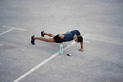A young boy is doing push up exercises in the street - p1166m2212924 by Cavan Images