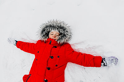 Girl in red warm clothing making snow angle during winter - p300m2256998 by Oxana Guryanova