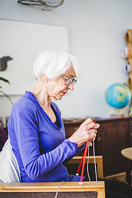 Senior woman knitting while sitting on chair in nursing home - p426m2018522 by Maskot