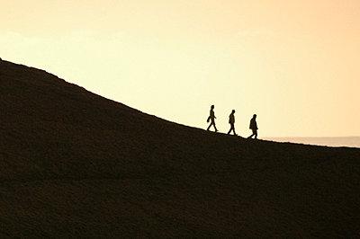 Drei Männer gehen eine Düne hinab - p567m667705 von AURELIAJAEGER