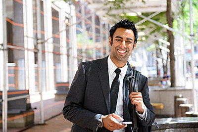 Businessman with cellphone and backpack - p924m711163f by Matt Dutile