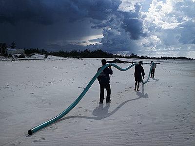 Three Vietnamese men carry a long green pipe along the shore of Dong Hoi under a dramatic sky, Quang Binh Province, Vietnam, Southeast Asia - p934m893105 by Boris Zuliani