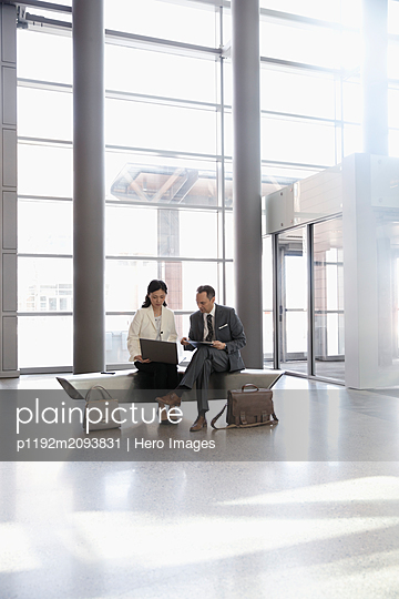 Business people meeting, using laptop in office lobby