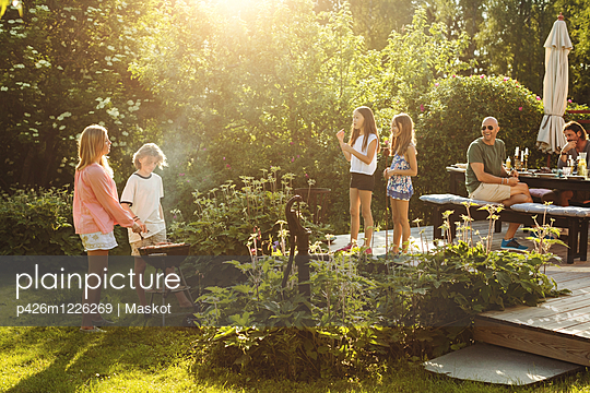 People enjoying summer during garden party on sunny day - p426m1226269 by Maskot