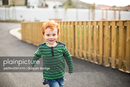 Boy running on road in residential area - p429m2091474 by Gonçalo Barriga