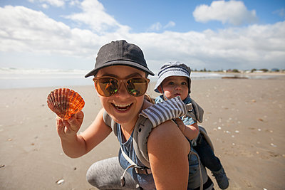 Portrait of mother holding seashell while piggybacking son at beach - p1166m1474582 by Cavan Images