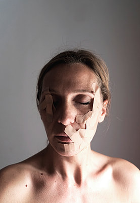 Woman with band aids on face - p1521m2126549 by Charlotte Zobel