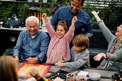 Cheerful multi-generation family playing board game on table while sitting in patio - p426m2159807 by Maskot