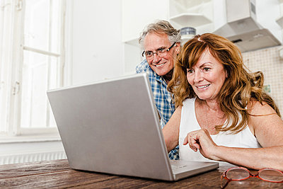 Older couple using laptop in kitchen - p429m659810f by Dan Brownsword