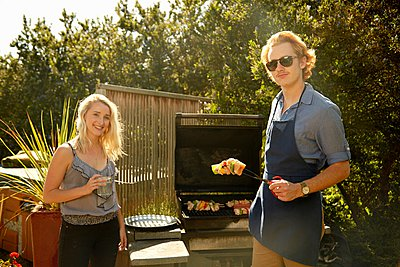 Couple at barbecue party - p924m1067458f by Stanton j Stephens