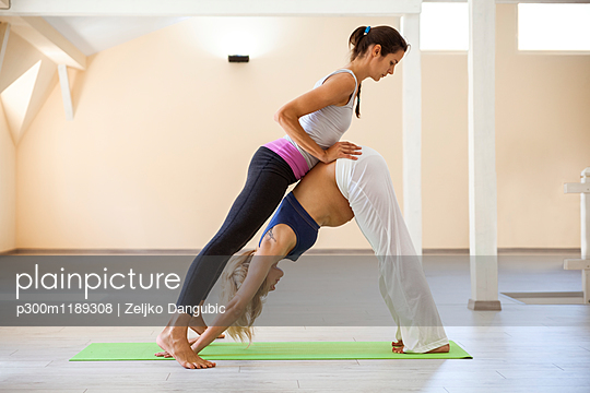 Prenatal yoga, female yoga instructor, downward facing dog pose