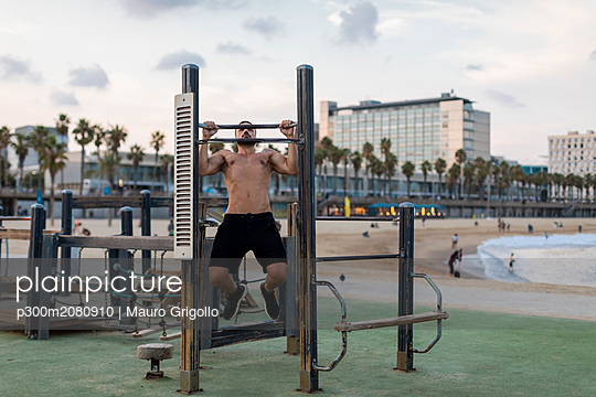 Barechested muscular man doing chin-ups on the beach - p300m2080910 by Mauro Grigollo