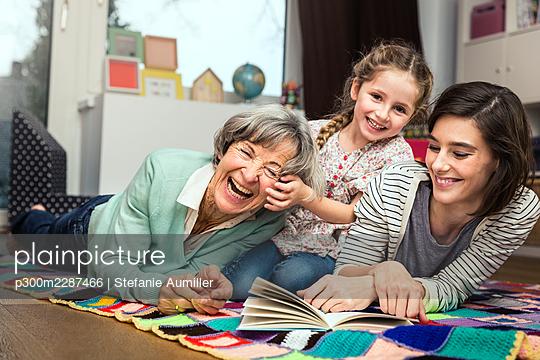 Grossmutter mit Tochter und Enkelin lesen im Kinderzimmer - p300m2287466 von Stefanie Aumiller