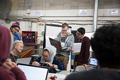Hacker teams brainstorming working hackathon at laptops in workshop - p1192m1202040 by Hero Images