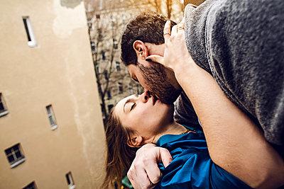 Mann küsst Frau am Fenster - p1301m1195891 von Delia Baum