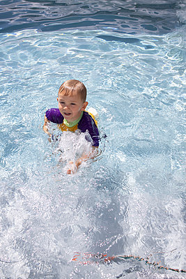Little boy splashing about in swimming pool - p1640m2254810 by Holly & John
