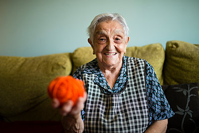 Portrait of smiling senior woman with ball of wool sitting on the couch at home - p300m2030055 von Ramon Espelt
