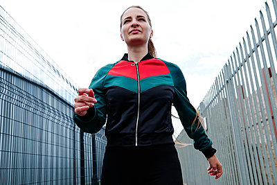 Female athlete amidst fences in front of sky - p300m2287159 by Angel Santana Garcia