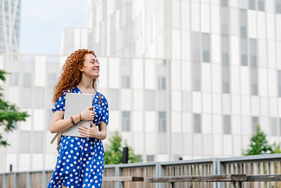 Smiling young woman with laptop walking in city - p300m2299197 by COROIMAGE