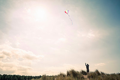 Silhouetted man flying a kite on Norfolk coast, UK - p429m1156410 by Dan Brownsword