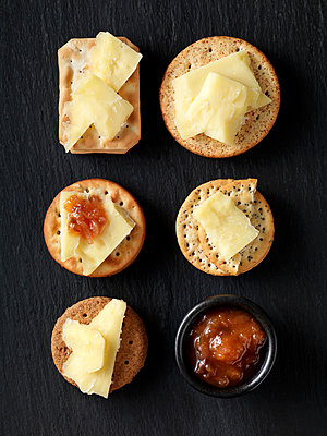 Still life of variety of cheese crackers with cheddar cheese and chutney on black slate, overhead view - p429m2068745 by Danielle Wood