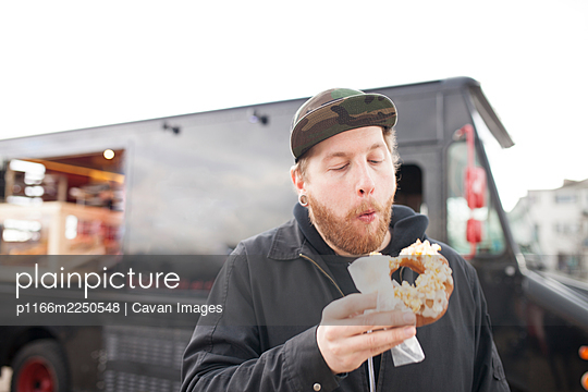 Hipster man eating donut from food truck - p1166m2250548 by Cavan Images