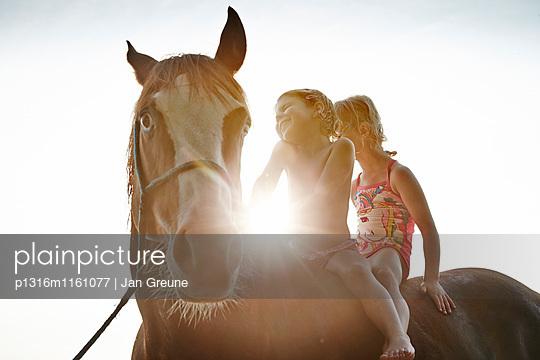 Zwei Mädchen auf einem Pferd am Starnberger See, Oberbayern, Bayern, Deutschland - p1316m1161077 von Jan Greune