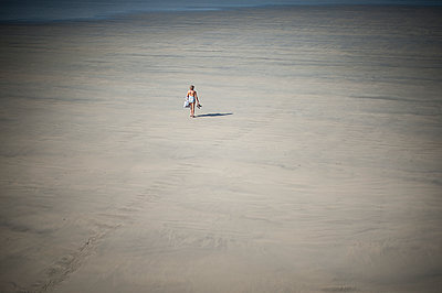 Single woman walking on beach - p1007m1216536 by Tilby Vattard