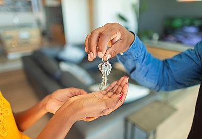 Close up man giving house keys to woman - p1023m2196707 by Paul Bradbury