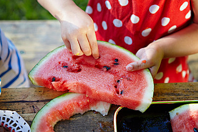 Girl eating water melon, removing pips, Munich, Bavaria, Germany - p1026m827663f by Dario Secen