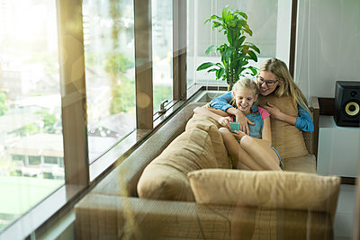 Mother and daughter in modern living room on a couch looking at smartphone together - p300m1587993 by Steve Brookland