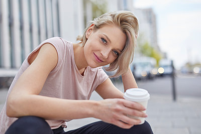 Portrait of smiling blond woman with takeaway coffee in the city - p300m2012928 von Philipp Nemenz