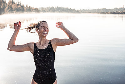 Cheerful woman wearing black swimsuit at a lake at morning mist - p300m2156890 by Wilfried Feder
