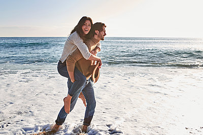 Boyfriend piggybacking smiling girlfriend while walking against sea - p300m2243397 by Veam